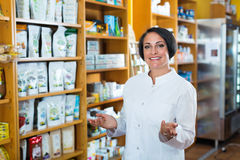 促进健康补充的白色外套的妇女在药房 免版税图库摄影