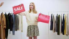 促进销售的愉快的年轻女人在衣物商店 股票录像
