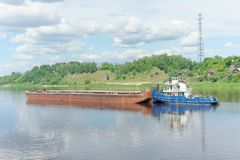 俄国伏尔加河 - 6月2日 2016年 河猛拉在用草和灌木盖的一家绿色银行附近推挤沿Volka河的一艘驳船 免版税库存照片