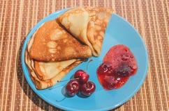 俄国传统盘薄煎饼用樱桃、果酱和牛奶 免版税库存图片