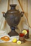 俄国俄国式茶炊、茶用柠檬在雕琢平面的玻璃与杯座和bublik 在葡萄酒样式的被设色的照片 免版税库存图片