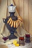俄国俄国式茶炊、茶用柠檬在雕琢平面的玻璃与杯座和bublik 在葡萄酒样式的被设色的照片 库存图片