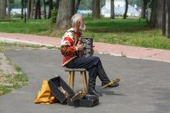 俄国全国服装的一个年长人在苏兹达尔,俄罗斯的播放手风琴 免版税图库摄影