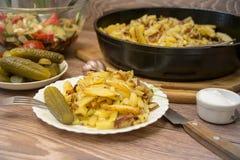 俄国全国烹调:油煎的土豆用酱瓜,大蒜 库存照片