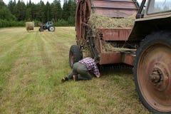 俄国农夫拖拉机司机修理在领域的打包机干草 图库摄影