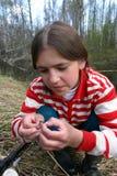 俄国农村夫人渔夫为钓鱼调整在勾子的诱饵 免版税图库摄影