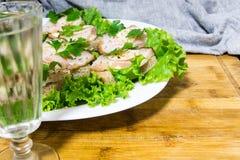 俄国和乌克兰人民的传统快餐假日 一个三明治用烟肉、大蒜和荷兰芹在g下玻璃  库存照片