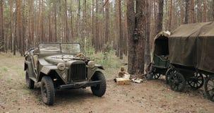 俄国在红色的森林WWII设备的苏维埃二战四轮驱动的军车Gaz-67汽车和农民推车 股票视频