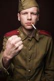 俄国士兵抽烟的香烟和威胁机智 免版税图库摄影