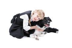 俄国女孩和黑白博德牧羊犬狗 免版税库存图片