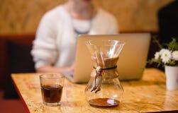 俄国女孩喝在一个咖啡馆的咖啡与膝上型计算机 免版税库存图片