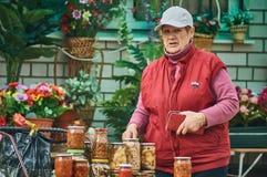 俄国妇女卖滚动了入罐头菜(卡卢加州地区) 库存照片
