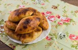 俄国小馅饼用在一个盘的圆白菜在五颜六色的布料 免版税库存照片