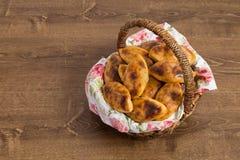 俄国小馅饼用在一个美丽的篮子的圆白菜在木 免版税库存照片