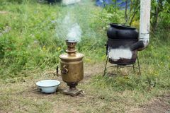 俄国式茶炊和火炉与锅炉食物的在草站立 图库摄影
