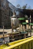 俄国式茶炊在一个树桩站立在庭院里 图库摄影