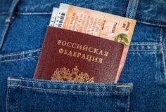 俄国护照和火车票在后面牛仔裤装在口袋里 免版税库存图片