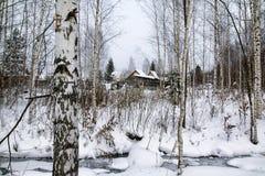 俄国村庄和木房子它的在一个冬天 免版税库存图片
