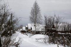 俄国村庄和木房子它的在一个冬天 库存照片
