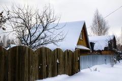 俄国村庄和木房子它的在一个冬天 库存图片