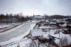 俄国村庄在与一条冻河和教会的冬天 免版税库存照片