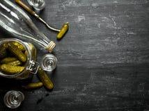 俄国样式 装瓶与小玻璃和酱瓜的伏特加酒 库存图片