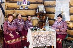 俄国民间服装的妇女坐在与俄国式茶炊的一张桌上 免版税库存照片