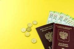 俄国现金和一些枚硬币 衡量单位在200卢布 在黄色背景的俄国护照 免版税图库摄影