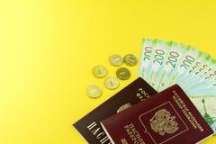 俄国现金和一些枚硬币 衡量单位在200卢布 在黄色背景的俄国护照 库存图片