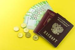 俄国现金和一些枚硬币 衡量单位在200卢布 在黄色背景的俄国护照 免版税库存照片