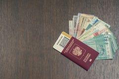 俄国生物统计的护照特写镜头与里面的登舱牌的和捆绑在桃花心木桌上的亚洲金钱 库存图片