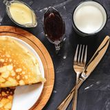 俄国盘薄煎饼、牛奶、果酱、白色巧克力、毛巾、握持热锅的布垫子、刀子和叉子的顶视图 库存图片