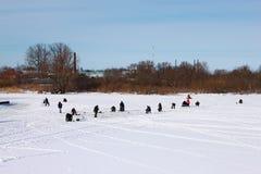 俄国省的居民在一条小结冰的河的冰钓鱼在冬天 免版税库存图片