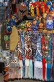 俄国纪念品例如五颜六色的披肩,围巾,绘了matryoshkas、装饰小袋子、钱包和军事头饰谎言o 免版税图库摄影