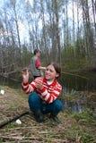 俄国青少年的女孩在一条农村河抓了小鱼 免版税库存图片
