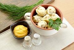 俄国饺子- pelmeni,在橙色碗*with芥末 免版税库存照片