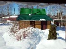 俄国banya的冬天视图从生存房子的冰柱的下面 库存图片