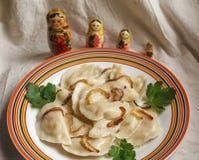 俄国vareniki用与matreshkas的土豆在背景 免版税图库摄影