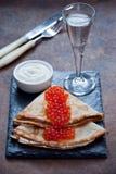 俄式薄煎饼用红色鱼子酱和伏特加酒 免版税库存图片