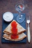 俄式薄煎饼用红色鱼子酱和伏特加酒 图库摄影