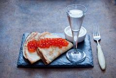 俄式薄煎饼用红色鱼子酱和伏特加酒 免版税库存照片