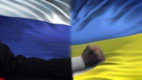 俄罗斯对乌克兰交锋,兴趣相冲突,在旗子背景的拳头 股票录像