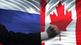 俄罗斯对加拿大交锋,国家分歧,在旗子背景的拳头 股票视频