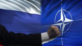 俄罗斯对北约交锋,国家分歧,在旗子背景的拳头 股票录像