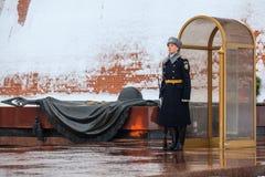 俄罗斯的总统军团的卫兵在无名战士附近坟茔的和永恒火焰在亚历山大在克里姆林宫墙壁附近从事园艺 库存照片