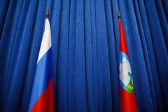 俄罗斯联邦和奥勒尔号地区旗子在蓝色背景 图库摄影