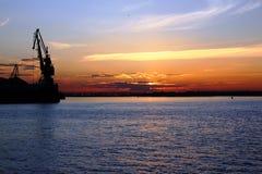 俄罗斯,伏尔加河:口岸起重机的剪影在日落的 库存图片