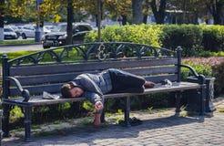 俄罗斯,克拉斯诺达尔2018年9月29日流浪汉在一条长凳睡觉在城市 免版税库存图片