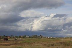 俄罗斯,列宁格勒地区,2018年9月14日,俄国村庄 俄国有干草的村庄在夏天,干草堆和村庄 免版税库存照片