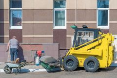 俄罗斯,喀山- 2019年4月12日:一个年长人在墙壁放置瓦片外面 免版税库存图片